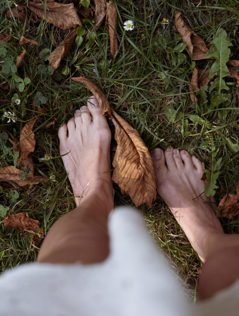 standing barefoot with autumn leaves on the fresh grass